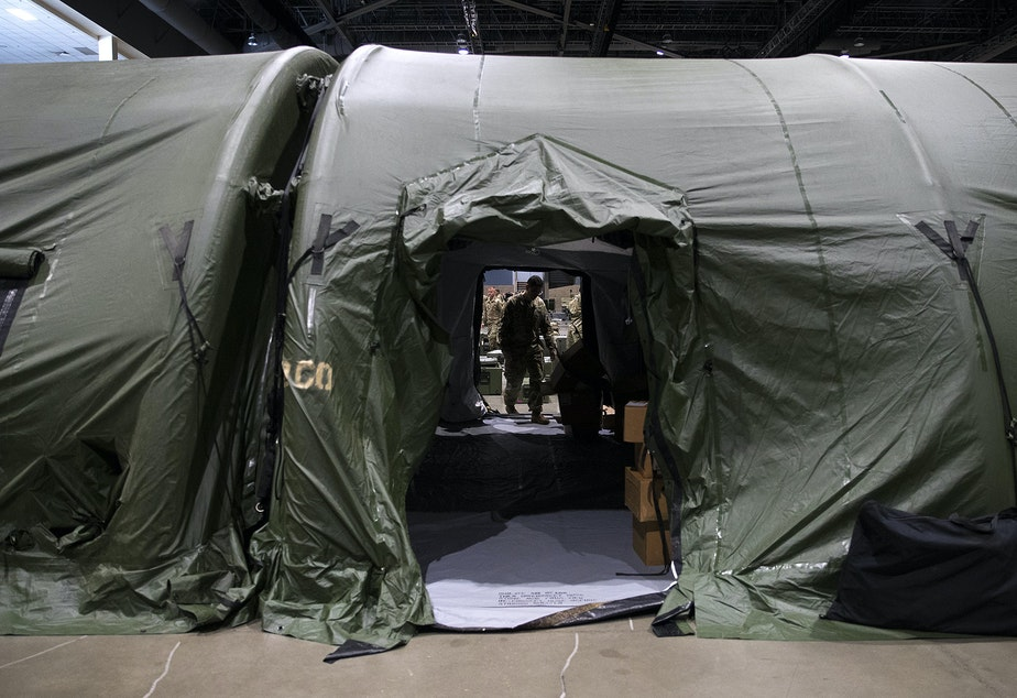 caption: U.S. Army soldiers are shown in the surgical area of a military field hospital set up by soldiers from the 627th Army Hospital from Fort Carson, Colorado, as well as from Joint Base Lewis-McChord on Tuesday, March 31, 2020, at the CenturyLink Field Event Center in Seattle.