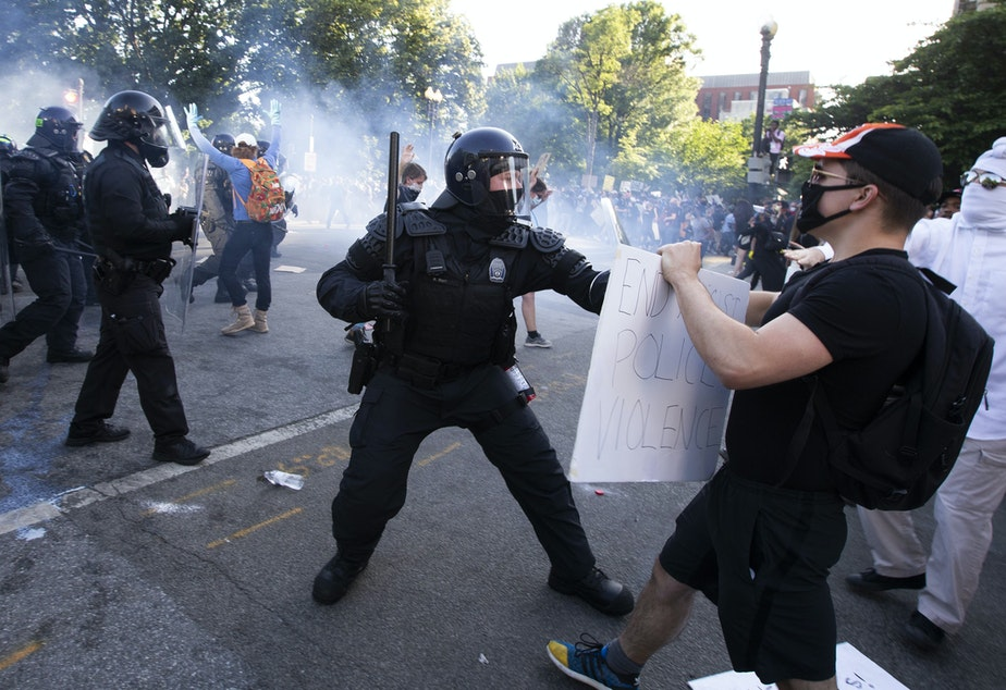 caption: A law enforcement officer raises a baton and tear gas is fired during protests near the White House on June 1.