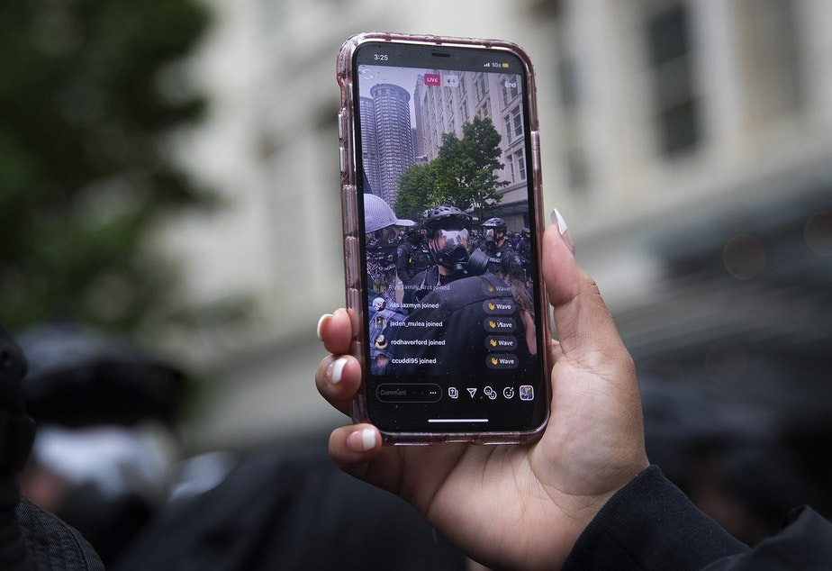 caption: A protester live-streams Seattle police officers on Saturday, May 30, 2020, at the intersection of 5th and Pine Streets in Seattle. Thousands gathered in a protest that turned violent following the police killing of George Floyd, a black man who was killed by a white police officer who held his knee on Floyd's neck for 8 minutes and 46 seconds, as he repeatedly said, 'I can't breathe,' in Minneapolis on Memorial Day.