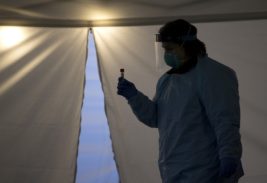 caption: FILE: A healthcare worker at UW Medicine's drive-through coronavirus testing clinic on Thursday, March 12, 2020, in Seattle.