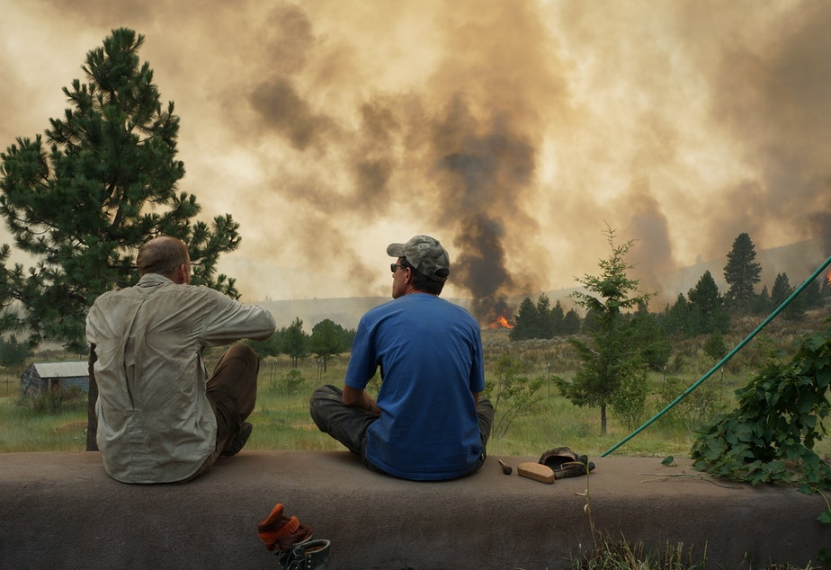 caption: Twig Wheeler (left) and his friend Edward Glidden look out over the Carlton Complex fire from Wheeler's home outside of Carlton, Washington.