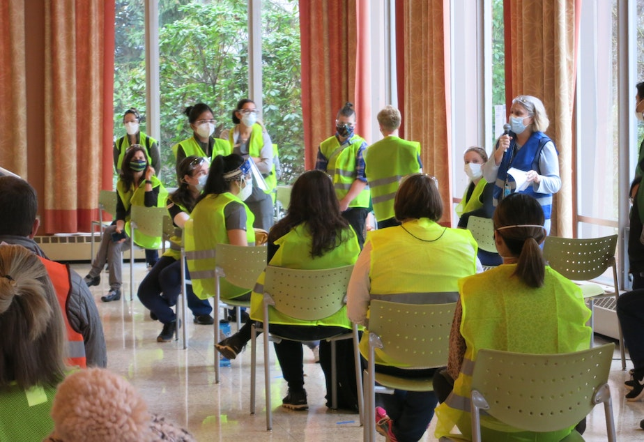 caption: Volunteers receive instructions at the beginning of their shift at a mass vaccination site run by Swedish at Seattle University, Saturday January 16, 2021.