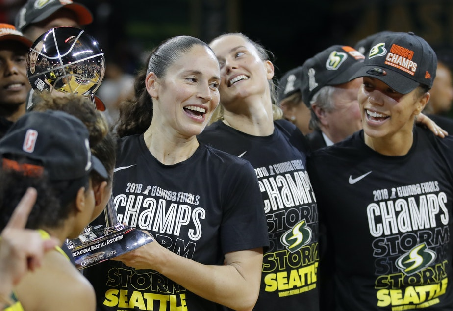 Seattle Storm guard Sue Bird, left, holds the championship trophy with her teammates Sami Whitcomb (center) and Alysha Clark (right) after winning Game 3 of the WNBA basketball finals, Wednesday, Sept. 18 2018, in Fairfax, Va. The Storm won 98-82.