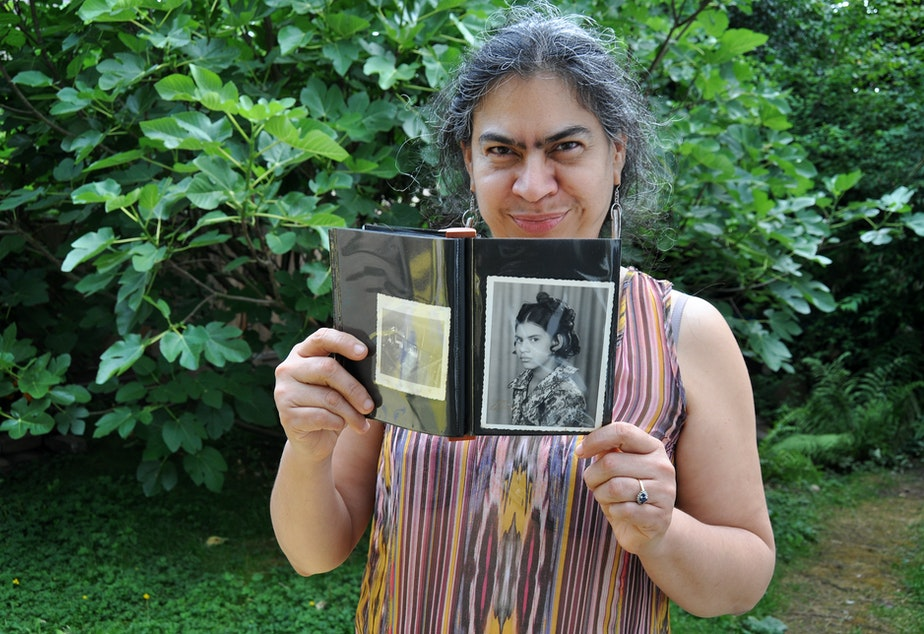 Milagros Ortiz holds a photo of herself as a child at her home in Vancouver, British Columbia. She left her home country, Nicaragua, at age eighteen.