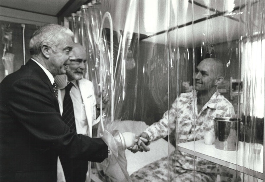 caption: Joe DiMaggio, Dr. E. Donnall Thomas, and patient Darrell Johnson in LAF (laminar airflow) room, 1978