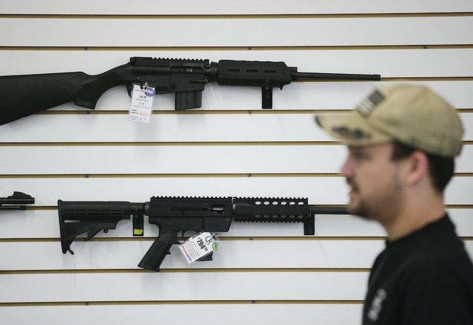 caption: FILE: In this Dec. 9, 2015, photo, a sales associate walks past semiautomatic rifles at Bullseye Sport gun shop in Riverside, Calif.