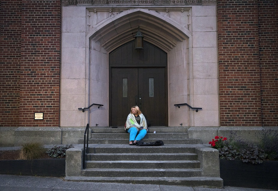 Milee Ballweg, 20, sits on the steps of a church in the University District where she sleeps just after 5:00 a.m. on Wednesday, July 11, 2018, in Seattle.