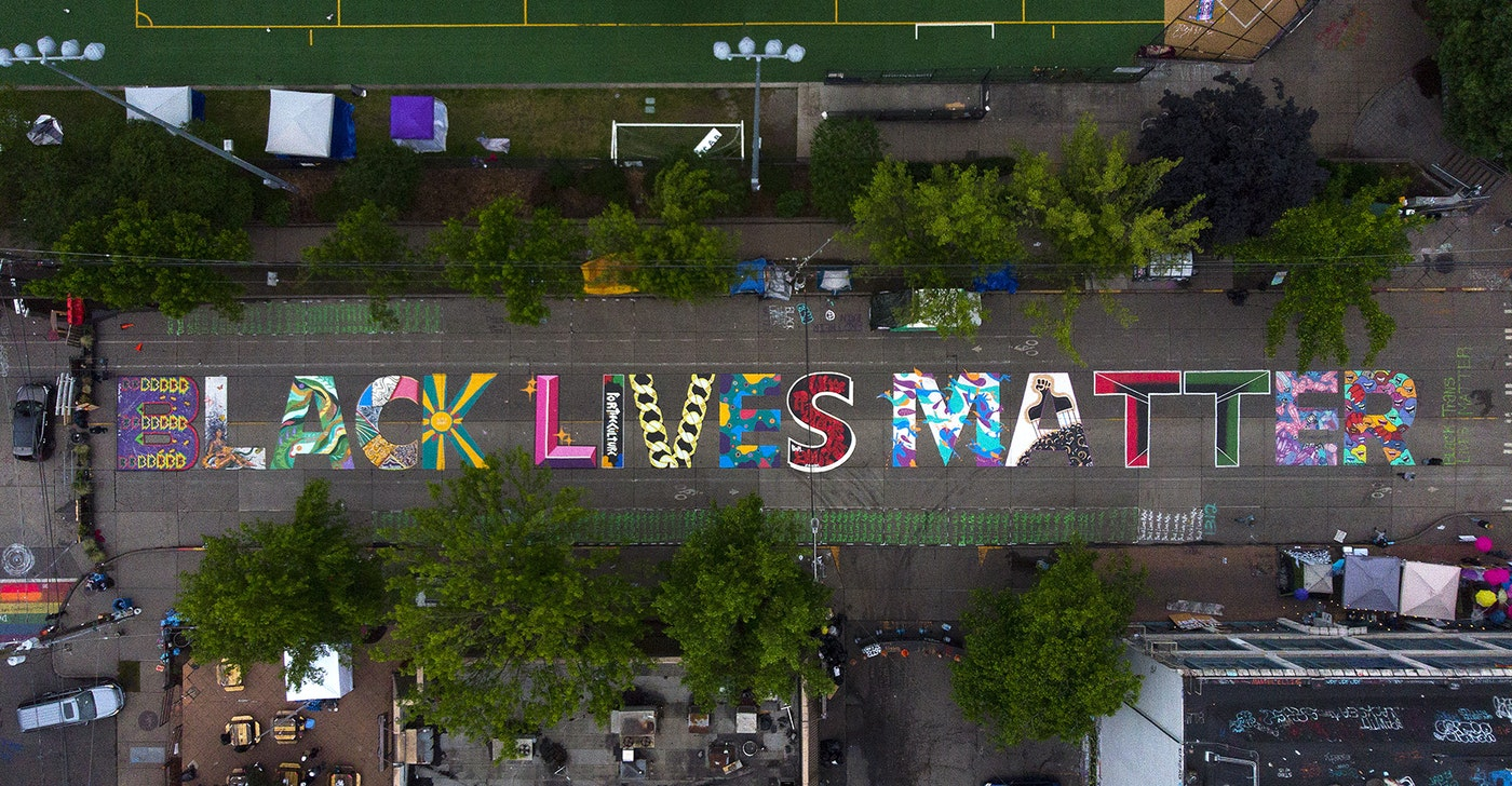 caption: The block-long Black Lives Matter street mural, beginning at 10th Avenue and East Pine Street, is shown on Saturday, June 13, 2020, inside the area known as the Capitol Hill Autonomous Zone, or CHAZ, in Seattle.