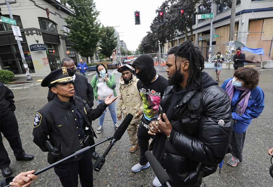 caption: Raz Simone, right front, and other activists speak with Seattle Police Chief Carmen Best, left, near a plywood-covered and closed Seattle police precinct behind them Tuesday, June 9, 2020, in Seattle, following protests over the death of George Floyd, a black man who was in police custody in Minneapolis.