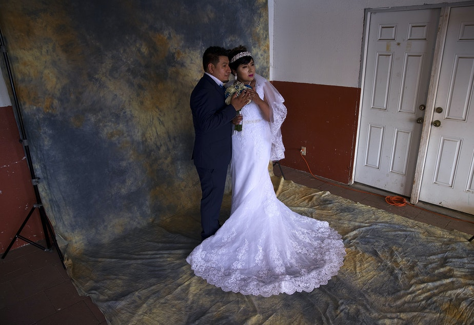 caption: Argimiro Nuñez and Honorina Hernandez pose for a portrait for their wedding photographer before a mass wedding ceremony where they were married along with 22 other couples on Sunday, June 2, 2019, at Our Lady of the Desert Church in Mattawa.