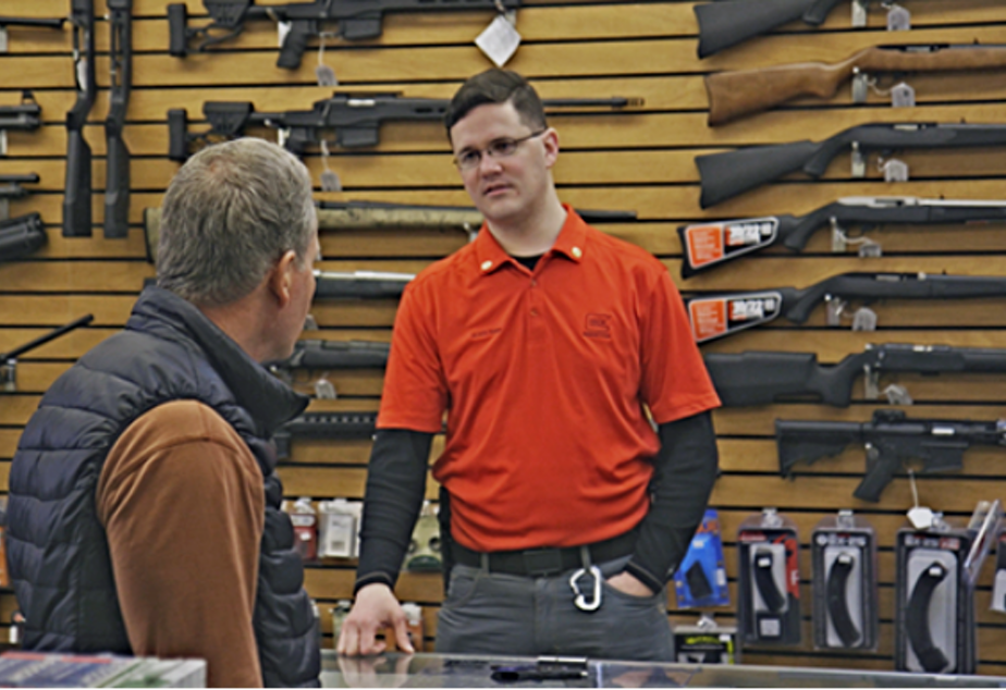 caption: Brett Bass, a gun retailer and coordinator of Forefront Suicide Prevention's Safer Homes, Suicide Aware program, talks with a customer about firearm safety.