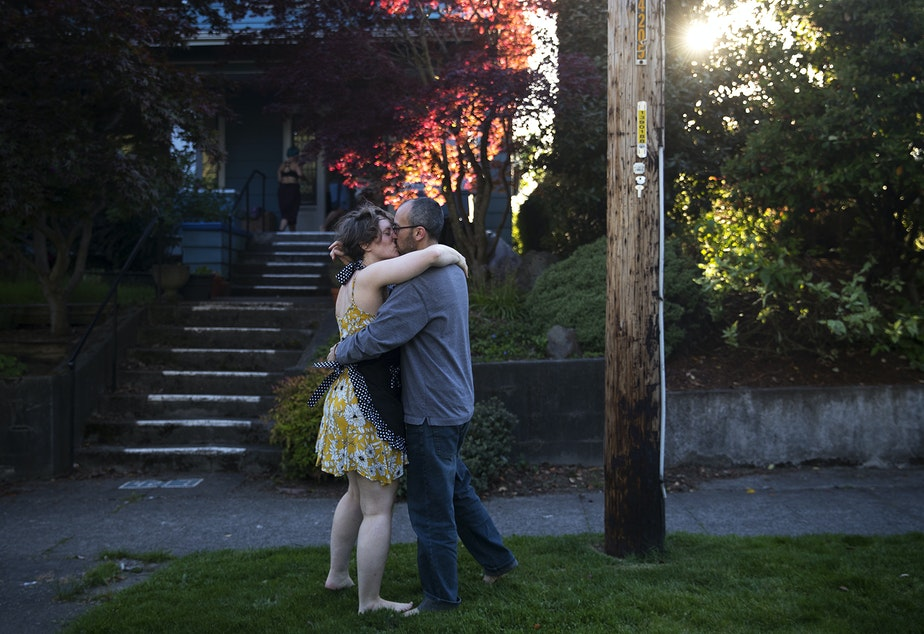 caption: Bethany Morrow, left, shares a kiss with partner Jeremy Lightsmith, right, after dancing along to the music as the Seattle Quarantine Parade drove through their neighborhood on Friday, May 8, 2020, in Seattle.