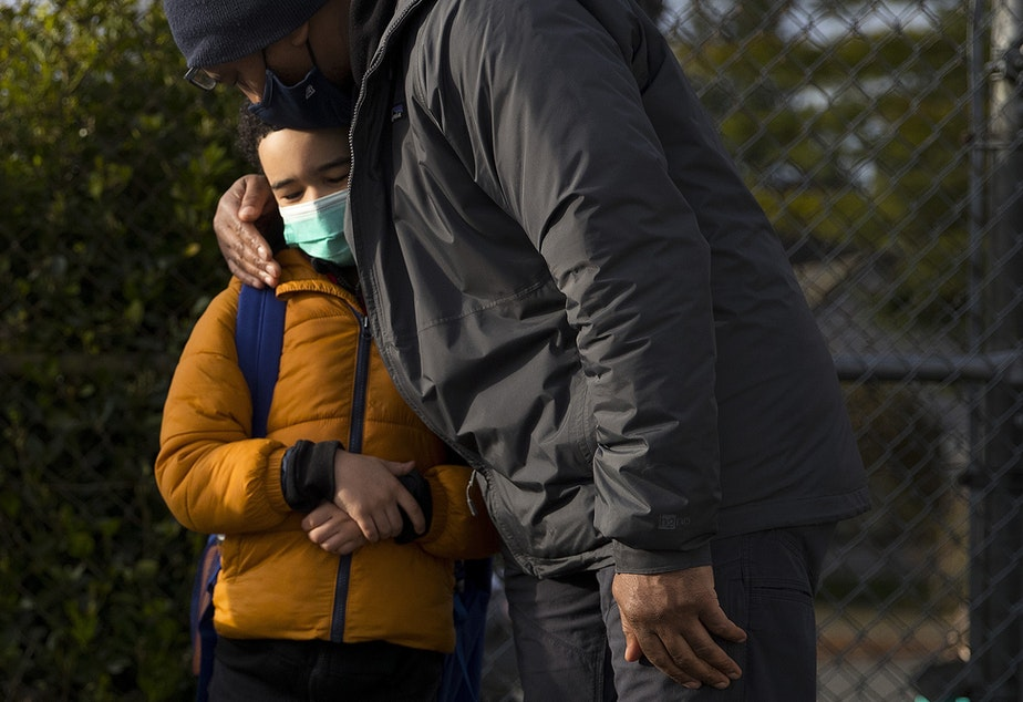 """caption: Derek Butler kisses his son, Mason Butler, a 1st-grade student at Northgate Elementary School, on the top of the head while saying goodbye on Monday, April 5, 2021, on the first day of in-person learning at the school in Seattle. """"I feel scared and a little happy,"""" said Mason. """"I missed making friends the most because I'm pretty good at doing that."""""""