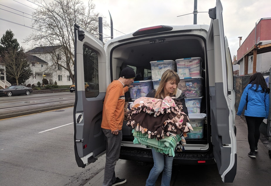 caption: Angela Harmon and fellow volunteers unpack blankets, diapers and other essentials in front of a tiny house village in Seattle
