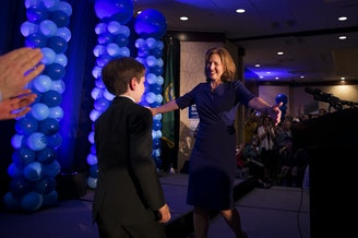 8th District candidate Kim Schrier celebrates on stage with her son, Sam, on Tuesday, November 6, 2018, at the Hilton in Bellevue.