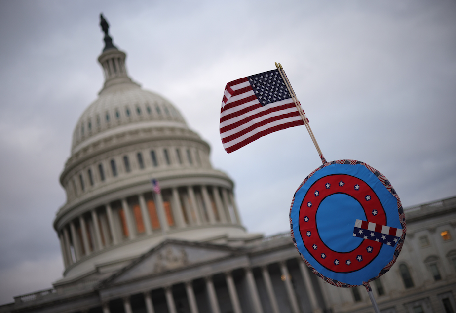 caption: Supporters of former President Trump fly a U.S. flag with a symbol from the group QAnon as they gather outside the U.S. Capitol Jan. 06, 2021 in Washington, D.C. (Win McNamee/Getty Images)