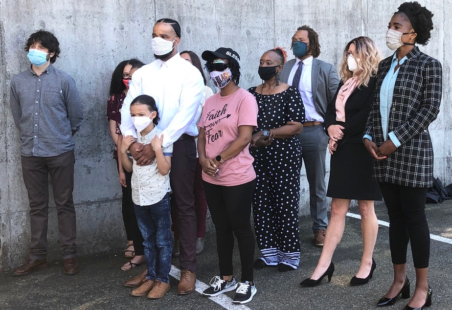 caption: Demonstrators, along with their attorneys and relatives, speak out against the Seattle Police Department's crowd control tactics against protesters during a press conference on Monday, June 22, 2020 in Bellevue. The boy, in front, encountered tear gas during a protest. The woman in the pink shirt is Nikita Tarver, who was hit in the eye with a rubber bullet, and may have lost sight in that eye.