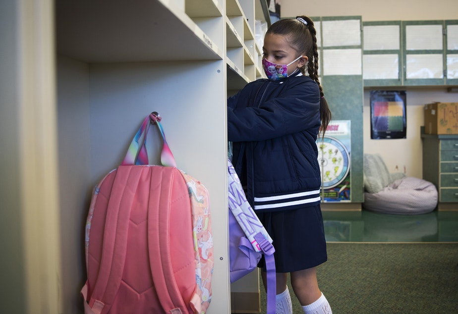 caption: Ximena Vaca Torres, 8, puts away her backpack on her first day of 3rd grade at Mount View Elementary school on Thursday, September 2, 2021, in Seattle.