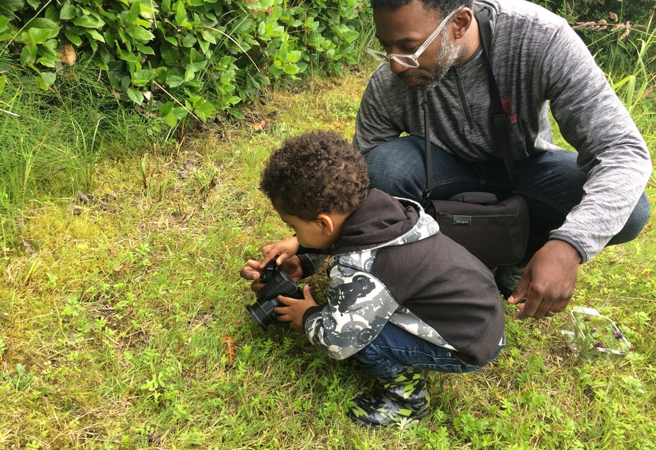 caption: Damon Taylor, a member of the West Coast Birders Facebook group, shows his son a slug at Westport Light State Park