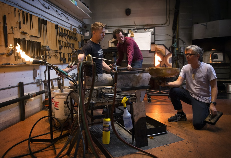 Assistants Janusz Pozniak, left, and Sean Albert, center, assist glass artist Preston Singletary, right, on Tuesday, December 11, 2018, as he sculpts a form to later do design work on at his studio in Seattle.