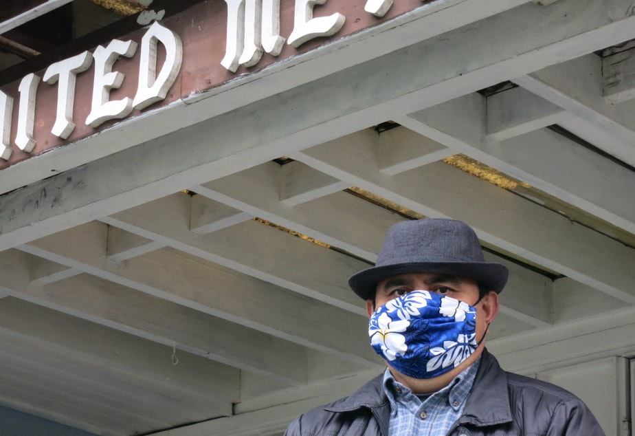 caption: El Dios Viviente pastor Gerardo Guzman poses for a photo in front of the church.