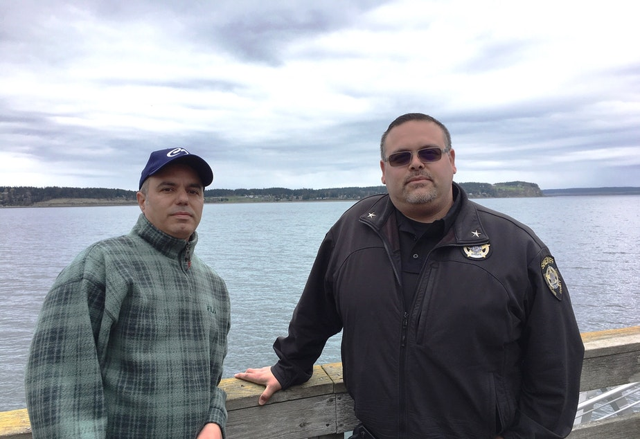 Fred Farris, the father of Keaton Farris, and Island County Jail Chief Jose Briones pose together on the Coupeville Wharf.