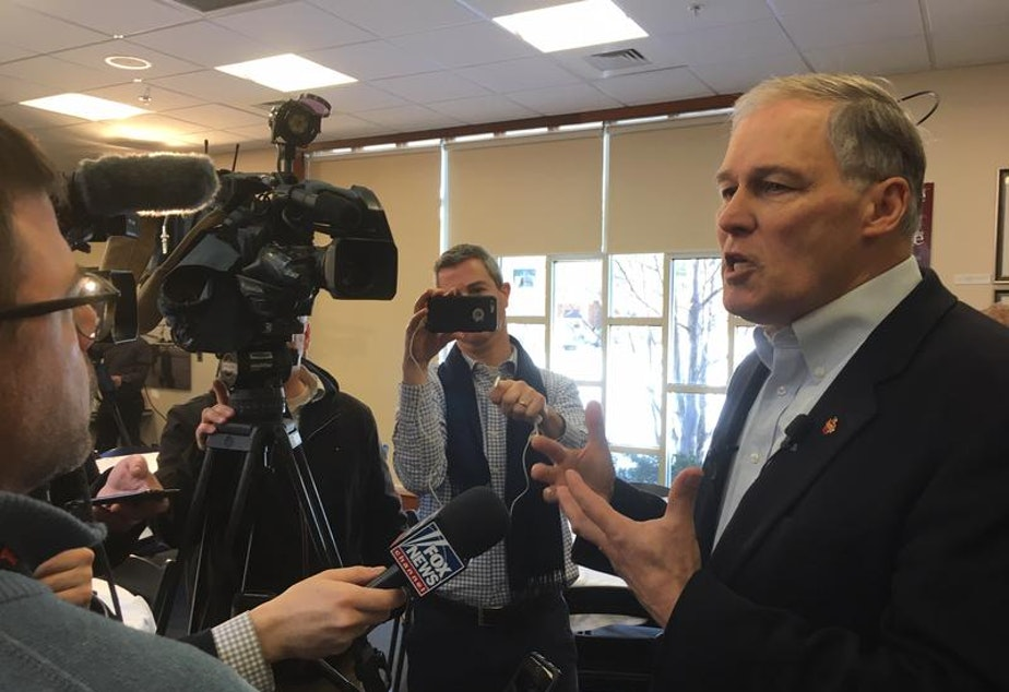 caption: Washington Gov. Jay Inslee speaks with reporters during a visit to the New Hampshire Institute of Politics in January.