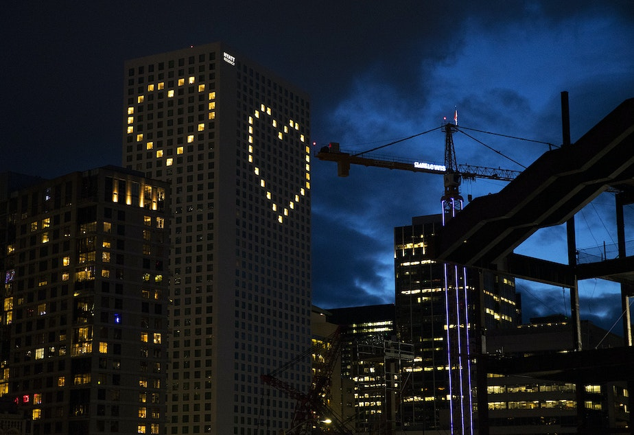 caption: Lit up windows make the shape of hearts on Tuesday, March 31, 2020, at the Hyatt Regency in Seattle.