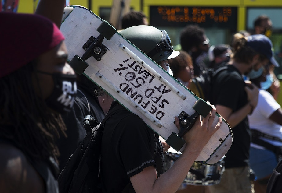 caption: A protester's skateboard reads 'Defund SPD 50% at least!' during the Defund The Police march and rally from the King County Juvenile Detention Center to Seattle City Hall on Wednesday August 5, 2020, in Seattle.