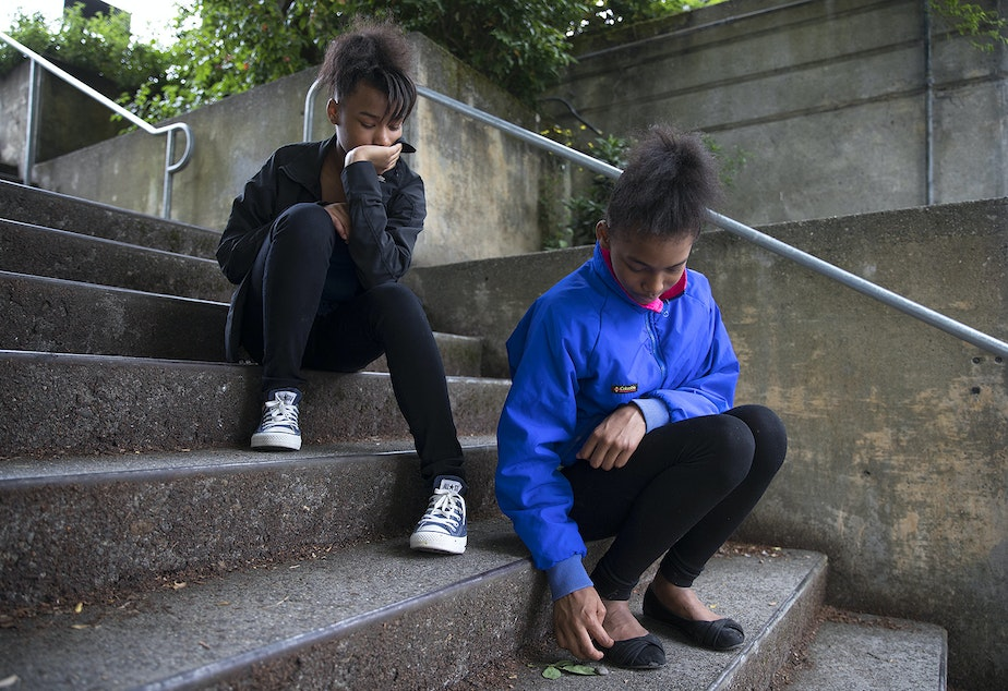 Twin sisters Makalah, 12, left, and Akalah, right, sit on the steps at the Solid Ground Brettler Family Place, on Monday.