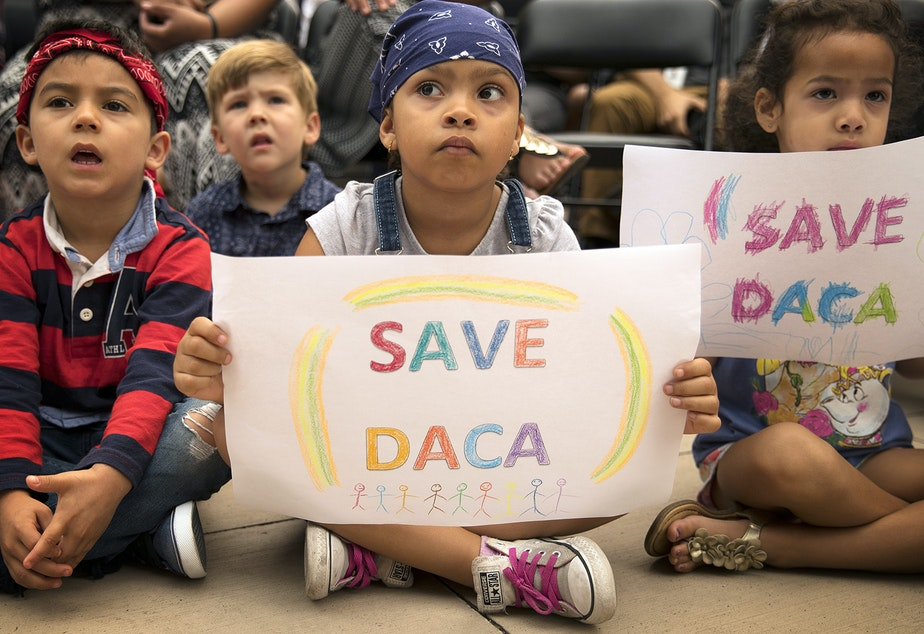 caption: Maya, center, a student at the Jose Marti Child Development Center holds a Save DACA sign during a community rally in support of DACA recipients on Tuesday, September 5, 2017, at El Centro De La Raza in Seattle.