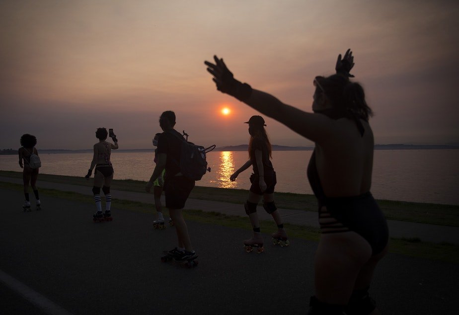 caption: Roller skaters skate along Alki Avenue Southwest during a Seattle Skates meet up as the sun sets on Wednesday, September 30, 2020, in Seattle.