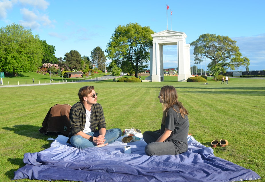 caption: When the U.S./Canada border closed, Ryan Hamilton and Savannah Koop had to postpone their wedding. Hamilton lives in Bellingham, and Koop lives just across the border in Canada. Since May 14, they've been able to meet up at Peace Arch Park, where pedestrians from each side can meet without officially crossing the border.