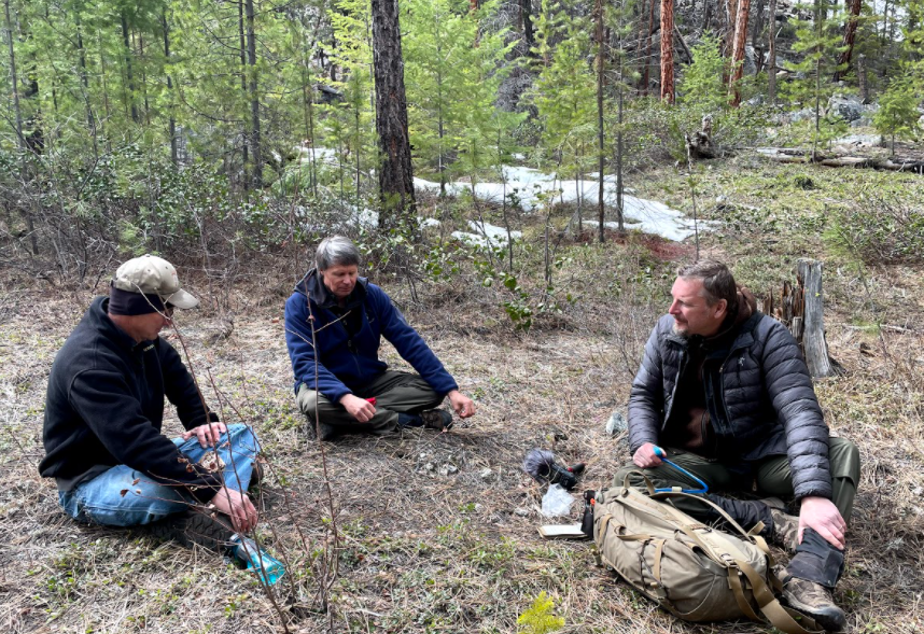 caption: Sitting near a rattlesnake den in the North Cascades of Washington state. Wildlife biologists John Rohrer (left) and Scott Fitkin (center).