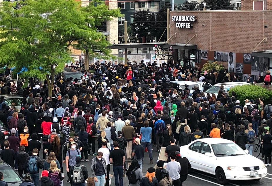 caption: Crowds gather at 23rd and Jackson in the Central District.