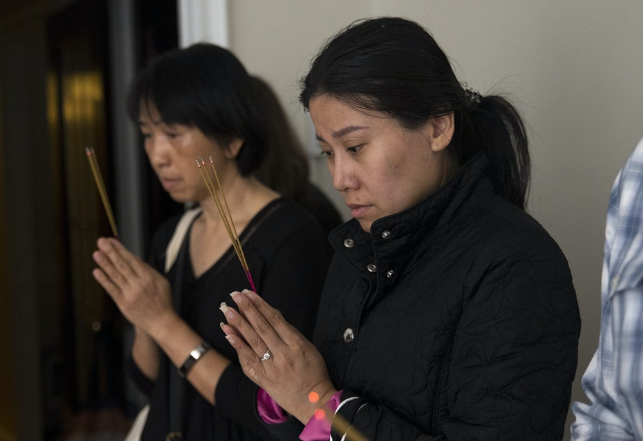 Nathathai Leenavarat, right, a cousin of Kornkamon Leenawarat, participates in a dedication ceremony with the Buddhangkura Buddhist Temple of Washington in the apartment of Kornkamon and Thiti-on on Wednesday, September 12, 2018, at the Malloy Apartments in Seattle.