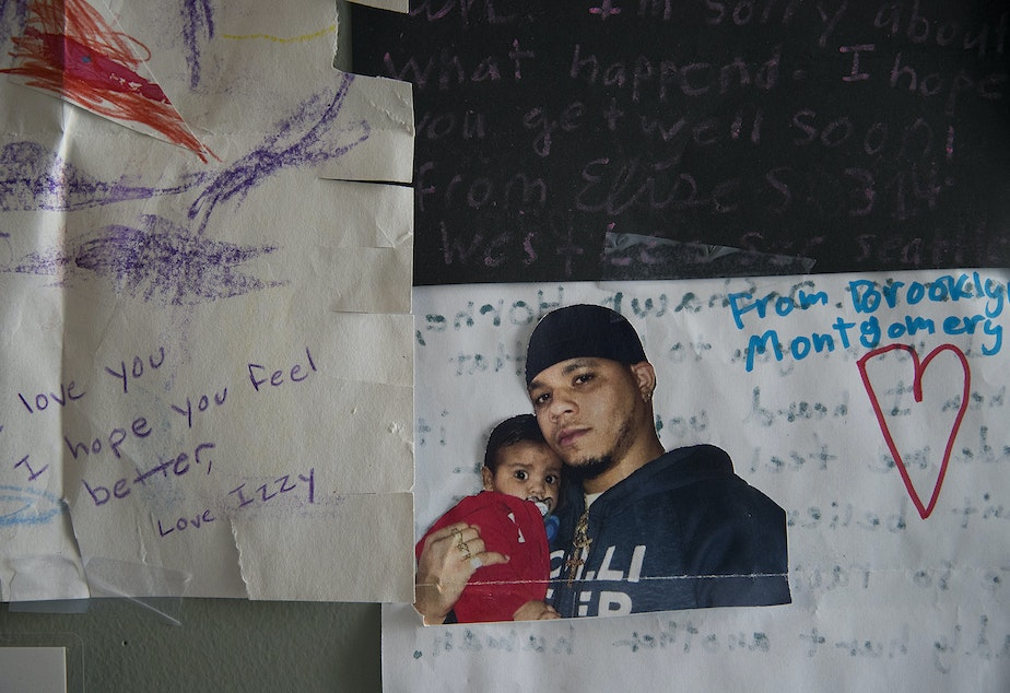 A picture of DaShawn Horne holding his son Deion is taped to a poster on the wall of his hospital room on Friday, April 13, 2018, at Harborview Medical Center in Seattle.