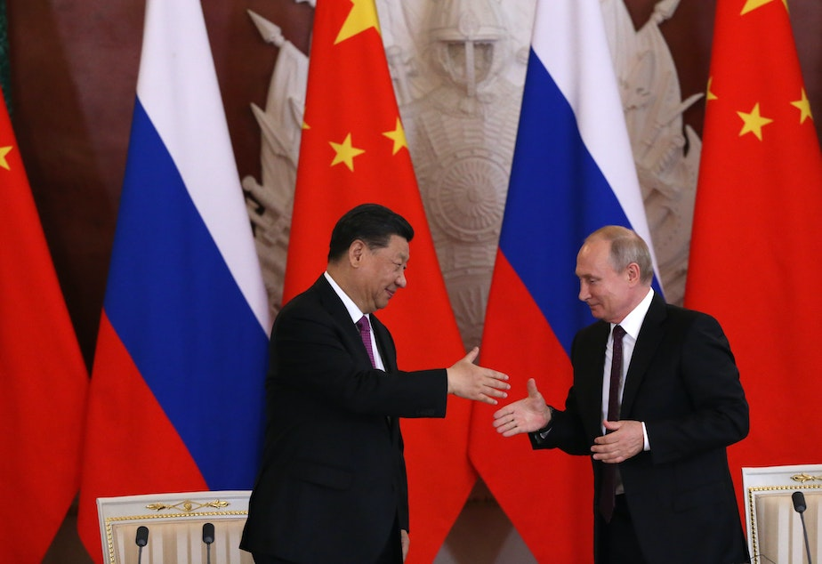 caption: Chinese President Xi Jinping and Russian President Vladimir Putin shake hands during their meeting at the Grand Kremlin Palace on Wednesday in Moscow.