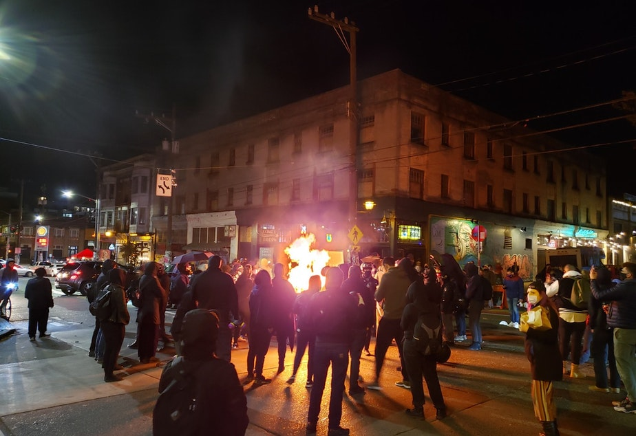 caption: A group of anti-fascist people protesting both Trump and Biden started a dumpster fire at the intersection of 10th and Pike on Capitol Hill Saturday night.