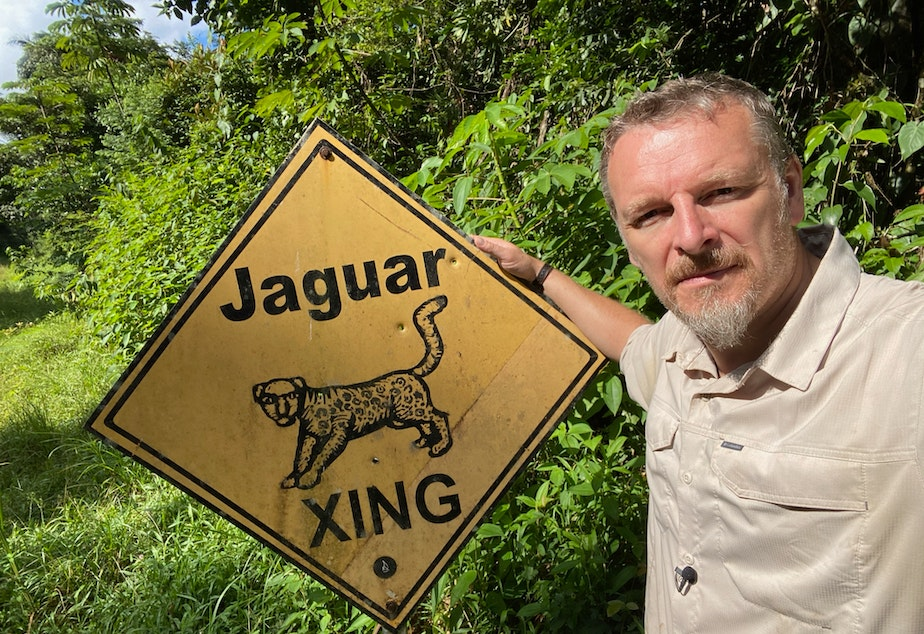 caption: Chris Morgan with a sign warning about jaguars in the jungles of Belize.