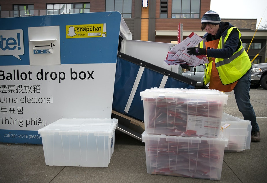 King County Elections employee Josephine Ruff unloads a  full ballot drop box outside of the Seattle Public Library in Ballard in November of 2017.