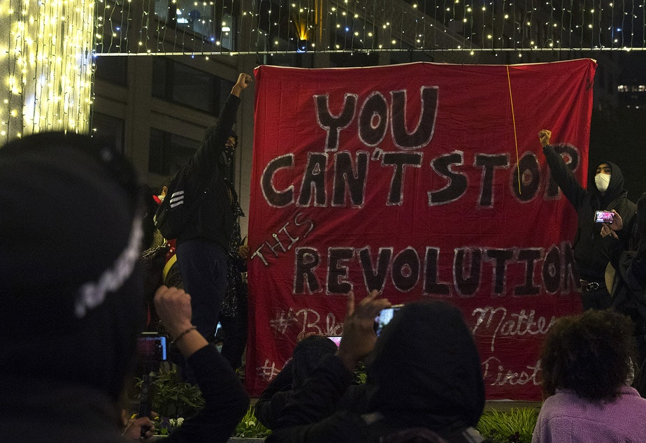 caption: Organizers raise their fists in the air after unfurling a banner reading, 'You can't stop this revolution,' on Monday, October 26, 2020, during the 150th day of protests for racial justice in Seattle at Westlake Park.