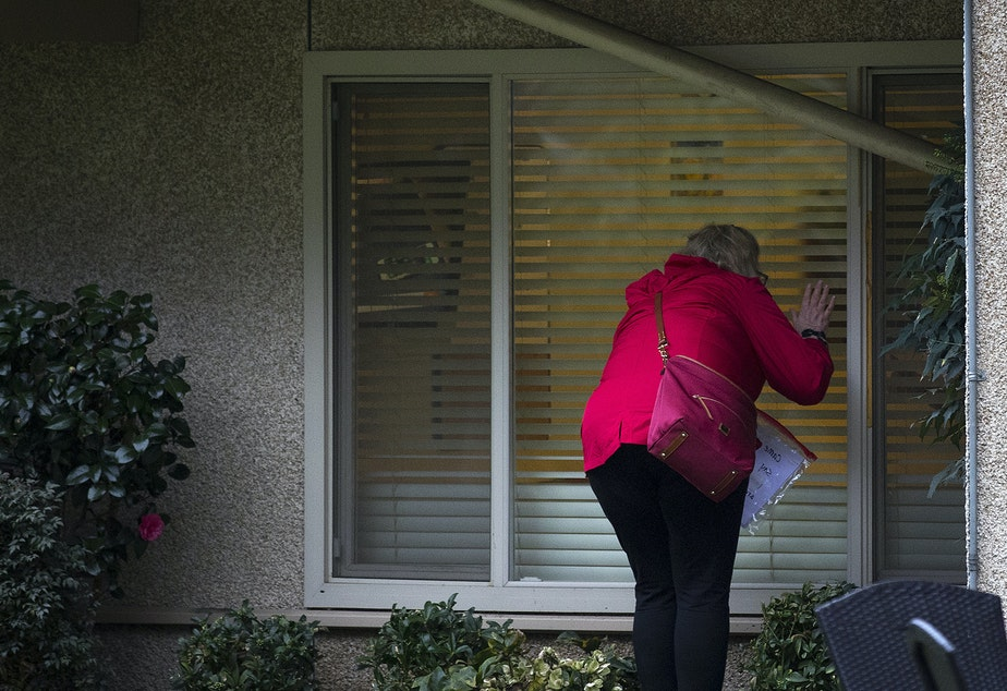 caption: A woman waves after knocking on her mother's window at the Life Care Center of Kirkland, the long-term care facility at the epicenter of the coronavirus outbreak in Washington state, on Monday, March 2, 2020, in Kirkland.