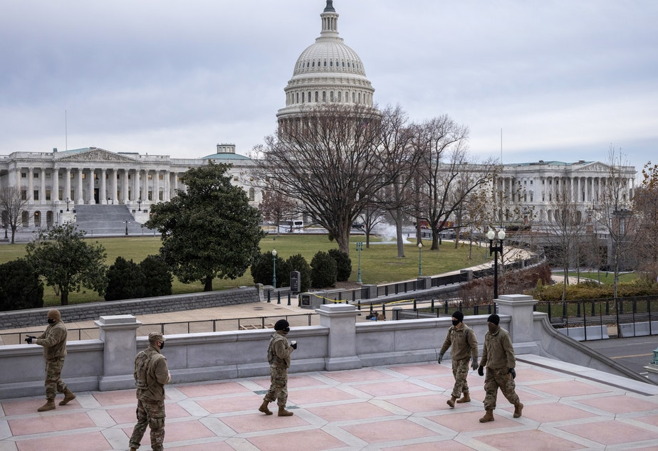 caption: Virginia National Guard troops stand watch near the U.S. Capitol Friday. House Speaker Nancy Pelosi has ordered the flags at the Capitol to be lowered to half-staff in Officer Brian Sicknick's honor.