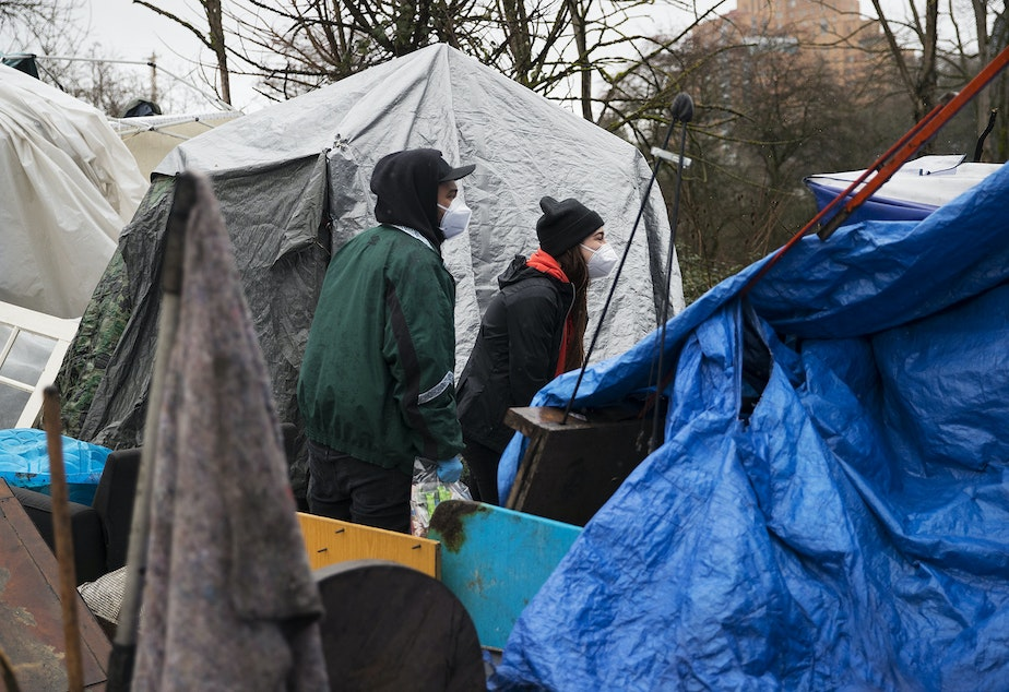 caption: Cass and Joscelyn DuVani redistribute resources including tents, sleeping bags, portable power packs, tarps, hot soup, clothing, and several other items to unhoused community members on Friday, March 5, 2021, near the intersection of 10th Avenue South and South Dearborn Street in Seattle.