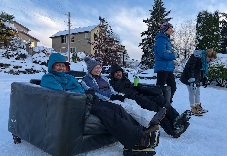 (Left to right) Sean Eley, Renee Grazer and Gabe Goldman set up a couch to sip coffee and watch their kids sled down Juneau in West Seattle.