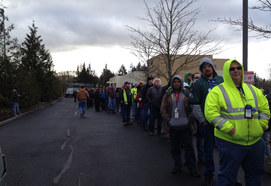 caption: Boeing machinists line up in Everett to vote on a contract offer Friday.
