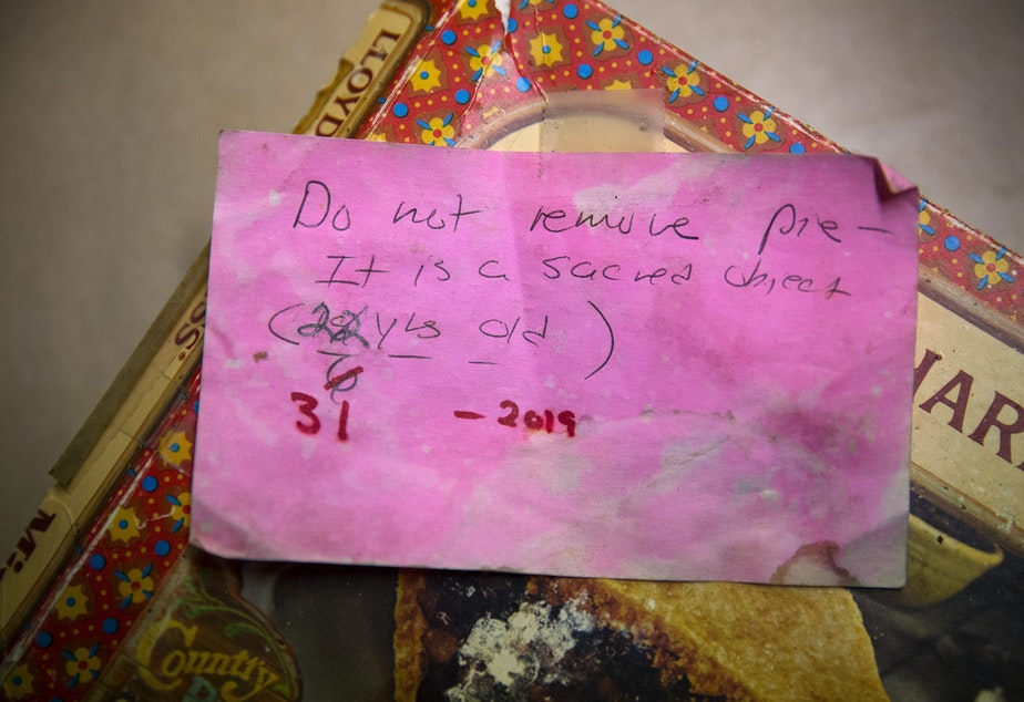 caption: A note taped to a mincemeat pie box reads 'Do not remove pie - it is a sacred object' on Friday, November 22, 2019, at the home of Sheila Kelly in Seattle. Her mother, Helen May Kelly, purchased the pie but died before the pie could be consumed. Kelly has kept the pie in her fridge ever since.