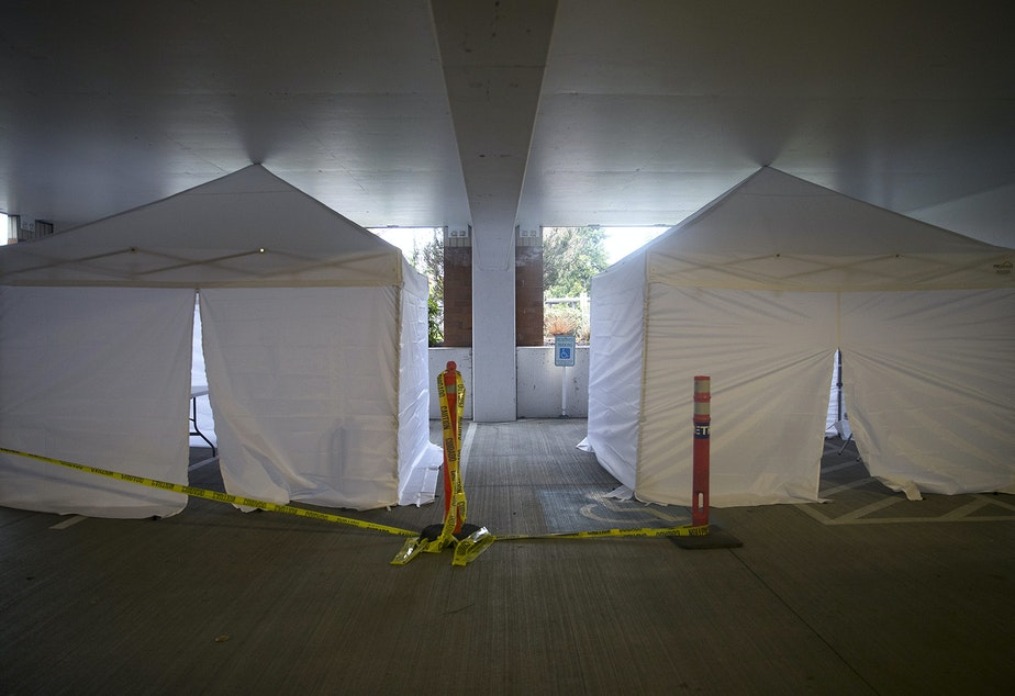 caption: White tents are set up in a parking garage of UW Northwest on Friday, March 6, 2020, in Seattle. Signs near the tents read 'Staff Testing.'