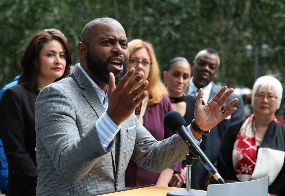 caption: Andre Taylor, of the community group Not This Time, speaks at a press conference on July 15, 2019.